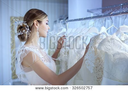 Young Beautiful Bride In A Wedding Dress Examines Wedding Dresses At The Counter In The Store.