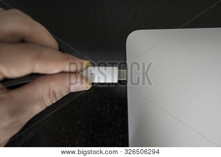 Male Hand Plugging White Usb-c Type C Cable Into A Port On A Grey Laptop Notebook Computer. Usb Type