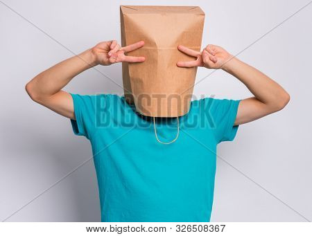 poster of Portrait of teen boy with paper bag over head making Victory gesture. Teenager cover head with bag showing victory sign posing in studio. Child pulling paper bag over head.