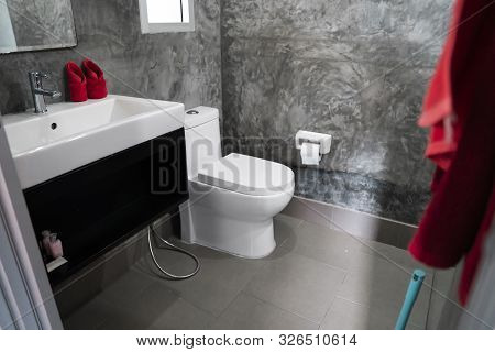 White Toilet In The Home Bathroom With A Sink And Red Towels On A Wall With Grey Tiles In Concrete S
