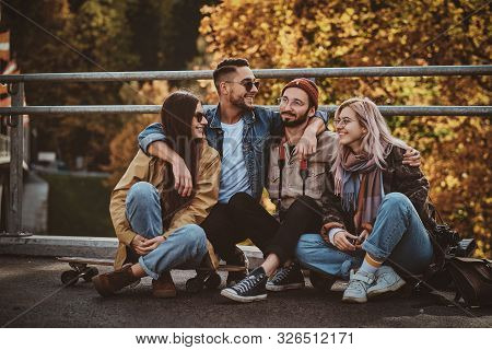 Happy Cheerful Friends Are Enjoying Autumn Walk In The Golden Leaves Park.