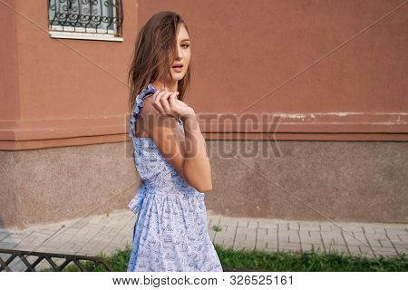 Slim Long Haired Model In Trendy Blue Summer Dress And Beige High Heels Walks As Strutting Out Onto