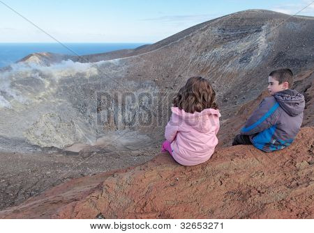 Girl and boy sitting on the rim of volcano crater of Vulcano island near Sicily Italy