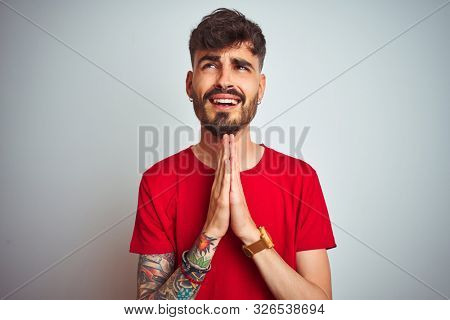 Young man with tattoo wearing red t-shirt standing over isolated white background begging and praying with hands together with hope expression on face very emotional and worried. Asking for forgivenes
