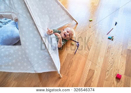 Young caucasian kid playing at kindergarten inside teepee. Preschooler boy happy at playroom with indian tent.
