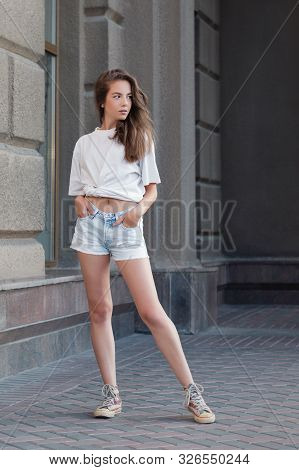 Full-length Portrait Of Trendy Stylish Girl In The City. She Walks On The Street And Turn Around On