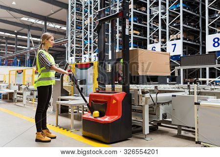 Storehouse Employee In Uniform Working On Forklift In Modern Automatic Warehouse.boxes Are On The Sh
