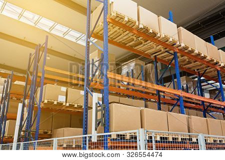 Large Hangar Warehouse Of Industrial And Logistics Companies. Long Shelves With A Variety Of Boxes.