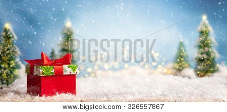 Beautiful winter background with red gift boxes on a wooden old desk, fir trees and blue sky. Winter, New Year and Christmas concept with snowy background.