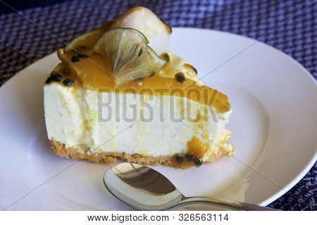 Decorated Homemade Passionfruit Cheesecake With A Spoon On A White Plate.