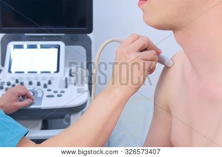 Doctor Makes Ultrasound Of Shoulder Joint To Man Using Ultrasound Scanner In Clinic, Closeup. He Run