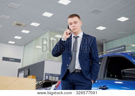 Kirov, Russia - February 26: Handsome Male Manager In A Suit And Car Lada In Showroom Of Dealership