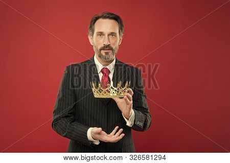 Reaching The Height Of Luxury And Elegance. Mature Man Holding Luxury Crown Jewel On Red Background.