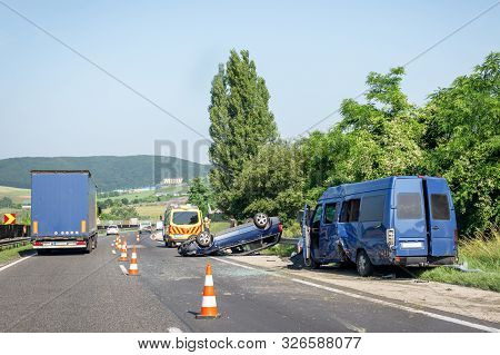 Car Crash Accident On Highway. Damaged Blue Minibus After Collision, Overturned Car And Ambulance Ca