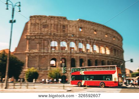 Rome, Italy. Colosseum. Red Hop On Hop Off Touristic Bus For Sightseeing In Street Near Flavian Amph