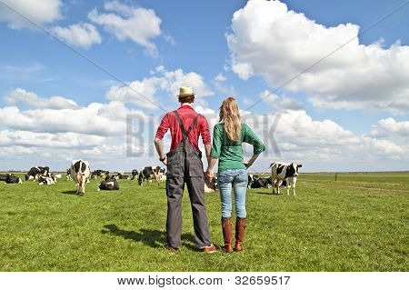 poster of The farmer and his wife proudly looking at their cows in the countryside from the Netherlands
