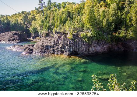 Clear Blue Water Of Lake Superior. Cliffs In The Marquette Presque Isle City Park Is A Popular Cliff