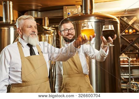 Two Specialists Standing With Glasses Of Beer, Looking At Glasses And Smiling. Brewery Workers In Wh