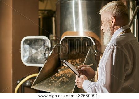 Confident Brewery Expert Watching Brewery Process And Writing. Handsome, Elderly, Bearded Brewery Wo