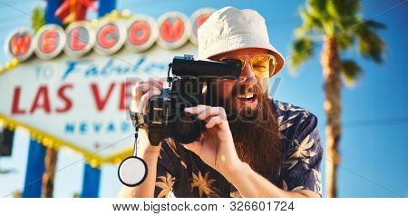 retro tourist with 80s camcorder in front of las vegas sign