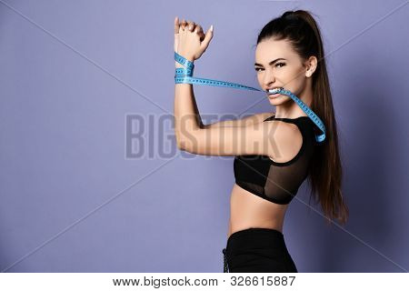 Determined Sporty Woman In Sportswear Shorts And Bralet With Her Hands Tied With A Measure Tape Is T