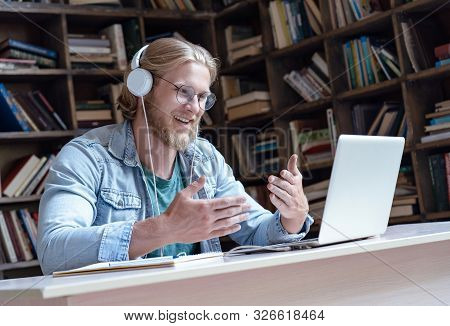 Happy Male Student Online Teacher Wear Headphone Talk Video Calling Looking At Laptop Computer Scree