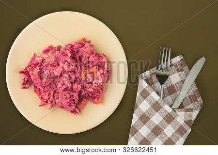 poster of herring under a fur coat on a beige plate. Herring under a fur coat on a grenn brown background. herring, beetroot, carrot, mayonnaise and onion salad top view.