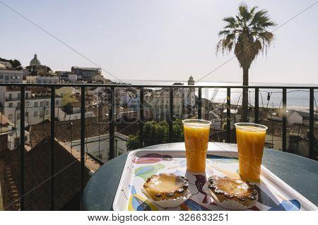 Breakfast With Pasteis De Belem And Orange Juice In The Open Cafe Overlooking Alfama District And Se