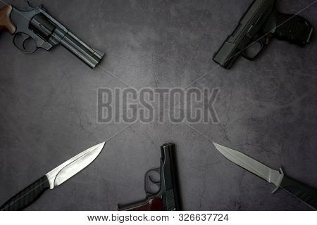 Firearms Laid Out Along The Line. Three Guns Pistols, Army Knives Close-up On A Gray Concrete Backgr
