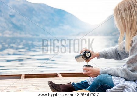 Cozy Winter Picnic On Wooden Pier By Sea, Blue Mountains. Woman Is Pouring Coffee From Thermos Into