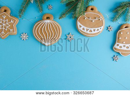 Christmas Mood. Tasty Gingerbread Cookies. Christmas Toys Hanging On A Blue Background On A Garland