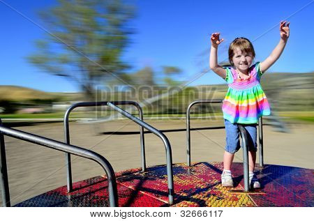 Little girl playing on merri-go-round at a park