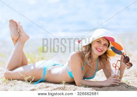The Girl Lies On The Beach With A Glass Of Juice. Pretty Woman 30-35 Years Old In Blue Bikini, Sunba