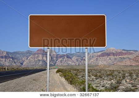 Blank brown highway sign with Nevada desert highway background.
