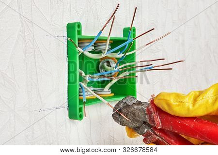 The use of end nippers for cutting the ends of copper wires during installation of a plastic rectangular electrical junction box and home electric wiring. Electrician uses wire cutters. poster
