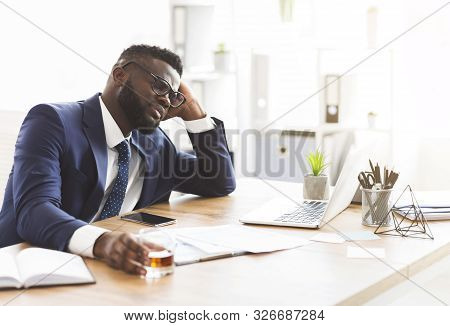 Things Getting Worse. Young African American Businessman Drinking From Stress, Holding Glass Of Whis
