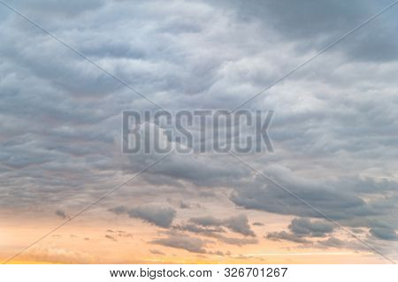Dark Clouds. Sky With Leaden Gray Clouds In The Evening At Orange-pink Sunset. Natural Background Fo