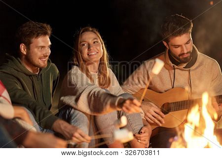 leisure and people concept - group of smiling friends sitting at camp fire, roasting marshmallow and playing guitar at night