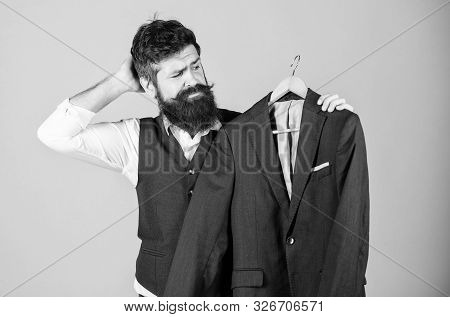 Thinking Of What To Wear To Formal Event. Hipster Choosing Formal Suit Jacket In Wardrobe. Bearded M