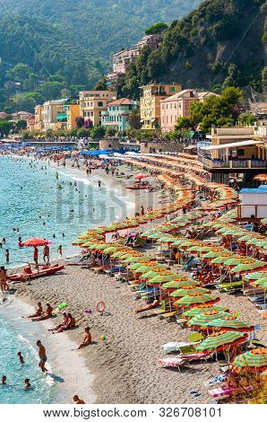 Monterosso Al Mare, Italy - September 02, 2019: The Famous Beach Full Of Deckchairs, Sun Umbrellas P
