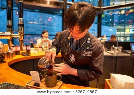 SHENZHEN, CHINA - CIRCA APRIL, 2019: barista prepare coffee at Starbucks Reserve Bar in Shenzhen. Starbucks Corporation is an American coffee company and coffeehouse chain.