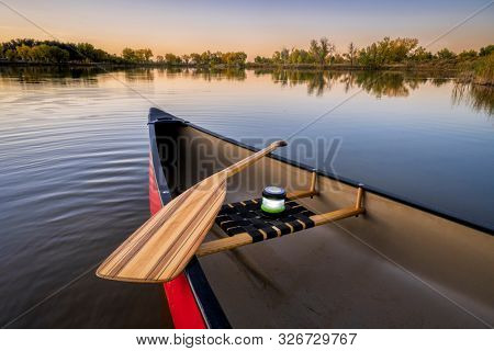 red canoe with a wooden paddle and lantern on a lake at dusk, fall scenery, wide angle view