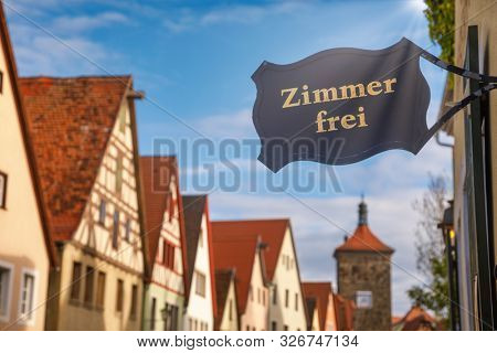 Zimmer frei (Rooms available) sign at a guesthouse or hotel with Half-timbered houses in background. Accommodation during travel by Romantic Road touristic route in Bavaria, Germany concept poster