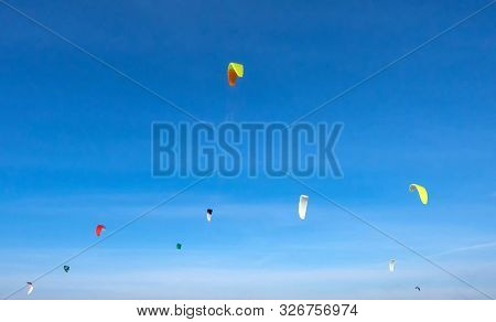 A Group Of Colorful Sailing Kites In The Sunny Sky.