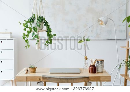 Stylish And Boho Home Interior Of Open Work Space With Wooden Desk, Chair, Lamp, Laptop And White Sh