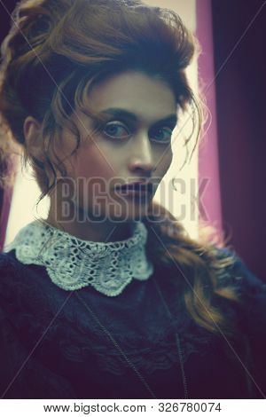 The Victorian era concept. Portrait of a beautiful woman in elegant historical dress and hairstyle posing in vintage interior. Baroque. Fashion.