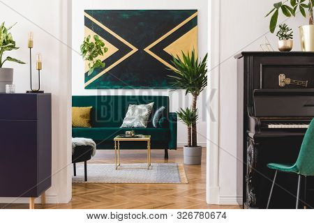 Stylish Luxury Home Interior Of Sitting Room With Green Velvet Sofa, Coffee Table, Shelf, Piano, Pou