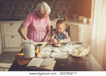 Background image cookbook, table, rolling pin, focus on the foreground. Girl and her grandmother cooking on kitchen.