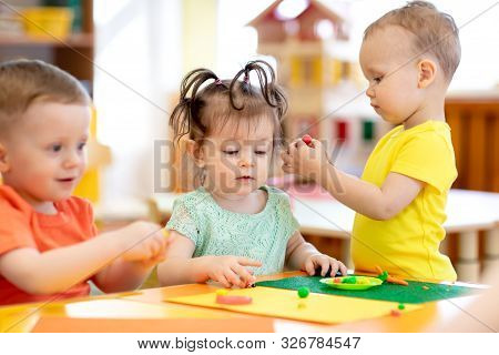 Three Children Toddlers Playing With Plasticine In Nursery Or Creche