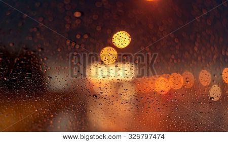 Orange Night Light Bokeh From Street Light On Traffic Jam Day. Rainy Day. Transparent Glass Window W